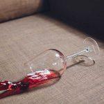 taça de vinho tinto derramada sob o sofá mostra como tirar mancha de vinho do sofá